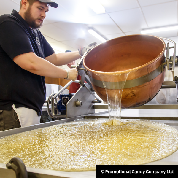 Mixed ingredients for rock sweets being poured on cooling slabs at the Promotional Candy Company factory.