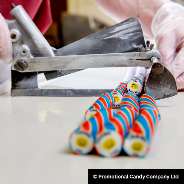 Cutting rock sweet into sticks of rock in the making process - made by Promotional Candy Company in Blackpool.